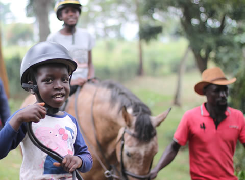 Children doing a pony ride with guides walking